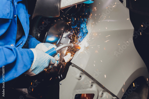 Fotografering professional repairman worker in automotive industry welding metal body car with sparks