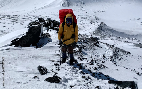 Fotografía Climber in a yellow jacket with an ice ax goes to the top of the volcano along a snow-covered trail