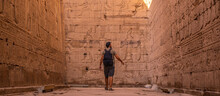 A Young Tourist In The Hieroglyphic Corridors Of The Edfu Temple In The City Of Edfu, Egypt. On The Bank Of The Nile River, Geco-Roman Construction, Temple Dedicated To Huros