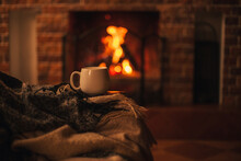 Mug With Hot Tea Standing On A Chair With Woolen Blanket In A Cozy Living Room With Fireplace.