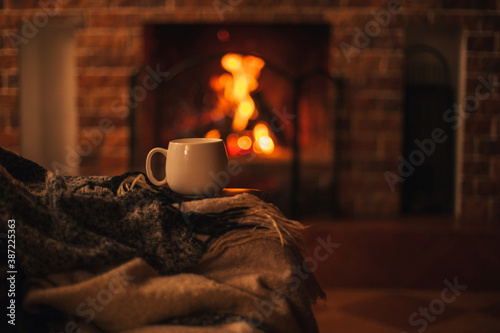 Obraz Mug with hot tea standing on a chair with woolen blanket in a cozy living room with fireplace. - fototapety do salonu