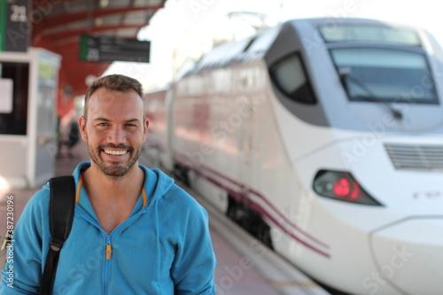 Obraz Blonde man smiling in train station - fototapety do salonu