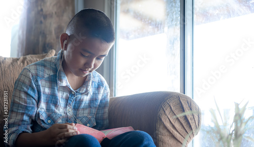 Fotografia Boy readinh Bible on sofa at home, Religion concept.