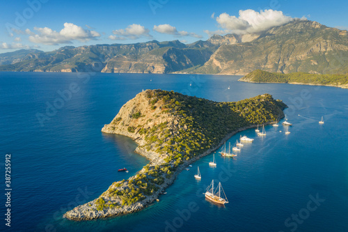 Obraz aerial view to island in sun light with yachts under blue sky and clouds on the tops - fototapety do salonu