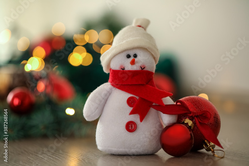 Snowman toy and Christmas balls on table against blurred festive lights, closeup Canvas