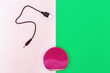 Leinwandbild Motiv Electric brush for deeply clean skin and usb cable for charging device. Red face brush on green and pink paper background with copy space. Beauty and skincare concept. Flat lay. Top View.