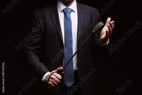 Fototapeta male dominant holds a leather whip Flogger for hard BDSM sex