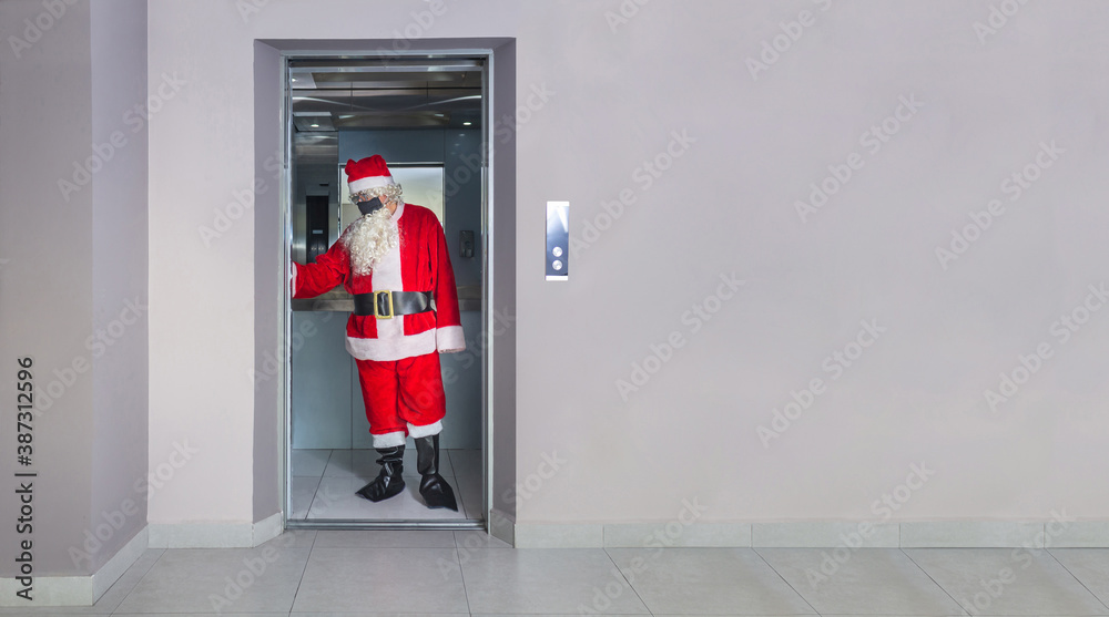Fototapeta Man disguised as Santa Claus with a mask, inside an elevator in a building on Christmas Day
