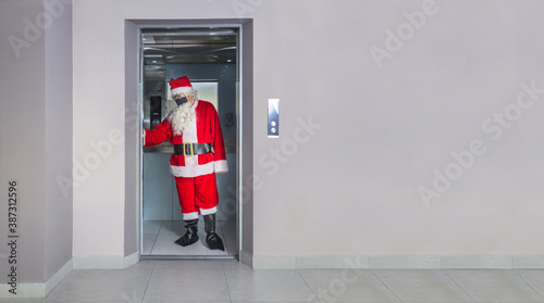 Leinwand Poster Man disguised as Santa Claus with a mask, inside an elevator in a building on Ch