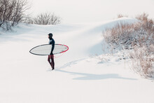 Snowy Winter And Surfer With Surfboard. Winter And Surfer In Wetsuit.