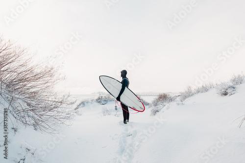 Billede på lærred Snowy winter and surfer with surfboard