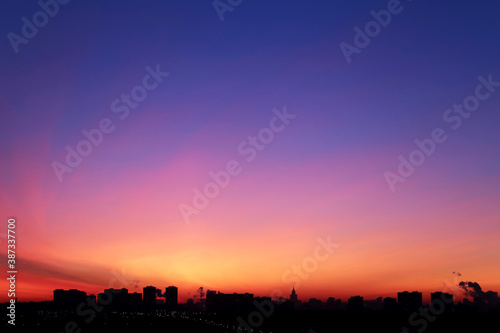 Obraz Sunrise over the city, scenic view. Pink-blue sky in soft colors sky above silhouettes of high-rise buildings, colorful cityscape for background - fototapety do salonu