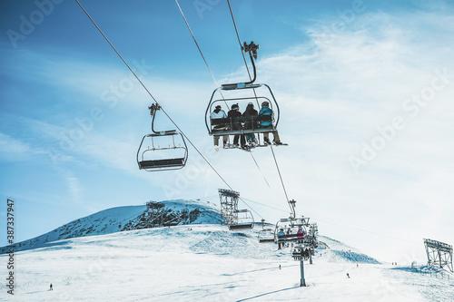 Fotografiet People on ski lift in winter ski resort  - Focus on guys sitting in cable car