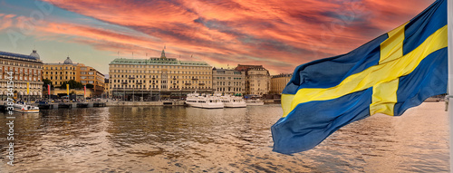 Golden hour panorama of historical Stockholm waterfront at sunset with national flag of Sweden on the first ground Fotobehang