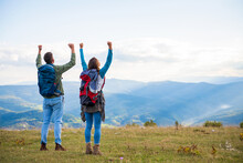 Happy Travelers Couple Conquered Top Of Mountain, Raises Hands Up