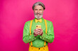 Leinwandbild Motiv Photo of funny white haired grandpa hold telephone look sly side empty space wear green shirt yellow suspenders bow tie pants isolated shine bright pink color background