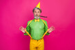 Leinwandbild Motiv Photo of funny white haired grandpa hold yellow suspenders blow noisemaker funky crazy birthday party surprise wear paper cap green shirt pants isolated bright pink color background