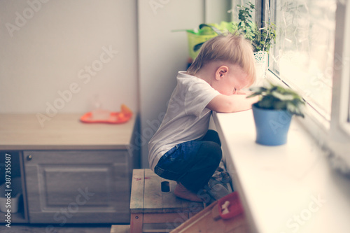 Fototapeta A lonely sad toddler toddler looks out the window with tears, a child in kinderg
