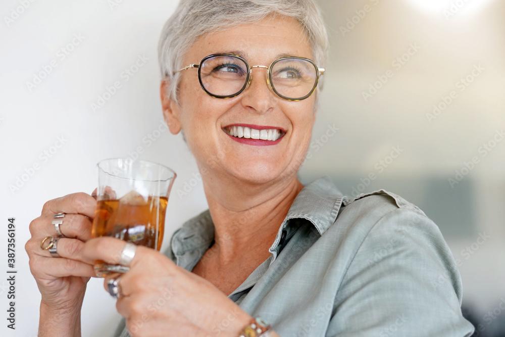 Fototapeta Cheerful 50-year woman drinking hot tea at home