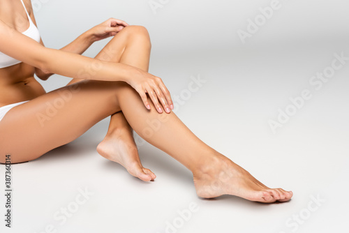 Obraz Cropped view of woman holding hands on knee, while sitting with smooth legs on grey - fototapety do salonu