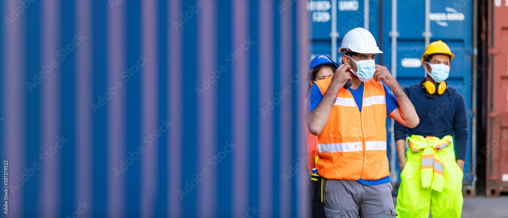 Fototapeta Group of professional team worker walking to working and wearing protection face mask during coronavirus and flu outbreak and wearing safety hardhat helmet at container yard or cargo warehouse