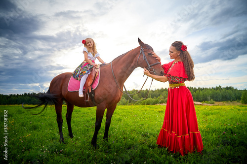 Fotografia, Obraz A woman and a girl in bright Gypsy dresses with a horse in a field with green grass