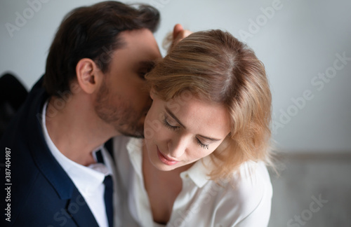 Leinwand Poster Business man kissing neck of young blonde woman closed eyes