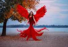 Young Beautiful Fantasy Woman Fallen Angel Lying In Air Near A Tree With Orange Leaves. Creative Red Costume, Huge Artificial Bird Wings And Elegant Dress. Magic Autumn Foliage. Photo Of Levitation.