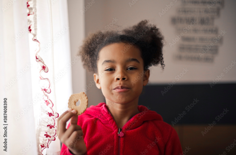 Fototapeta portrait of little girl while eating a cookie