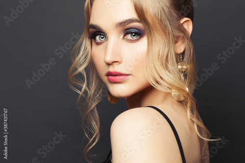 Fashion beauty portrait of perfect woman with blonde hairdo and makeup on black background - 387431767