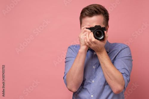 Obraz Traveler and photographer. Studio portrait of handsome young man holding photocamera taking photo. Yellow blackground. - fototapety do salonu