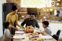 Happy African American Family Enjoying In Thanksgiving Lunch In Dining Room.