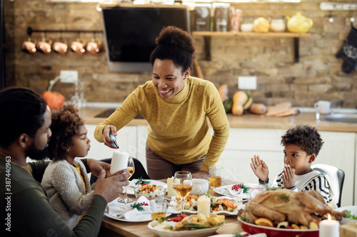 Tablou Canvas Happy African American family lightning candle during Christmas lunch at dining table