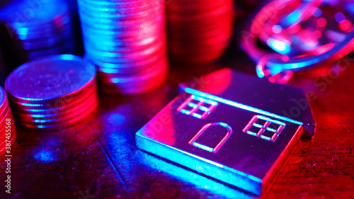 Gradient light color blue and red ray on house keychain decorate with coins stack on the table , banking technology concept, focus on keychain Wallpaper Mural