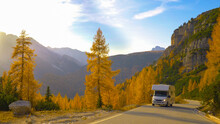 White Recreational Vehicle Drives Up Empty Mountain Road On A Sunny Fall Day