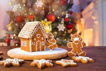 Homemade Gingerbread House On The Background Of A Decorated Christmas Tree And Unfocused Lights
