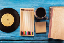 Black Coffee Cup, Vinyl Record, Book And Colorful Pencils On The Blue Wooden Table Background.