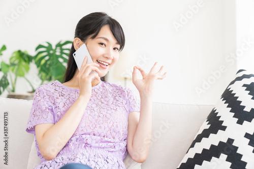 Vászonkép 部屋で電話をする女性