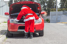 Santa Claus Checking His Car Engine In Front Of His Car That Is Damaged On Christmas