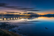 Wharf, reflections and sunrise over the bay