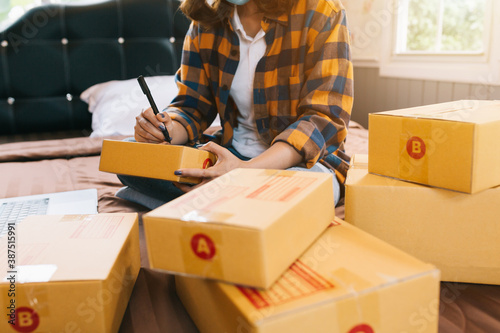 Obraz Close up Online shopping young women start small business in a cardboard box at work. The seller prepares the delivery box for the customer, online sales, or ecommerce. - fototapety do salonu