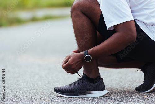Fotografie, Obraz Close up Asian sport runner black man wear watch sitting he trying shoelace runn