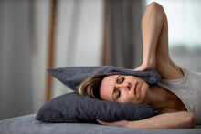 Sleepless Lady Covering Ears With Pillow. Noisy Neighbors, Tinnitus, Insomnia Or Stress Concept.