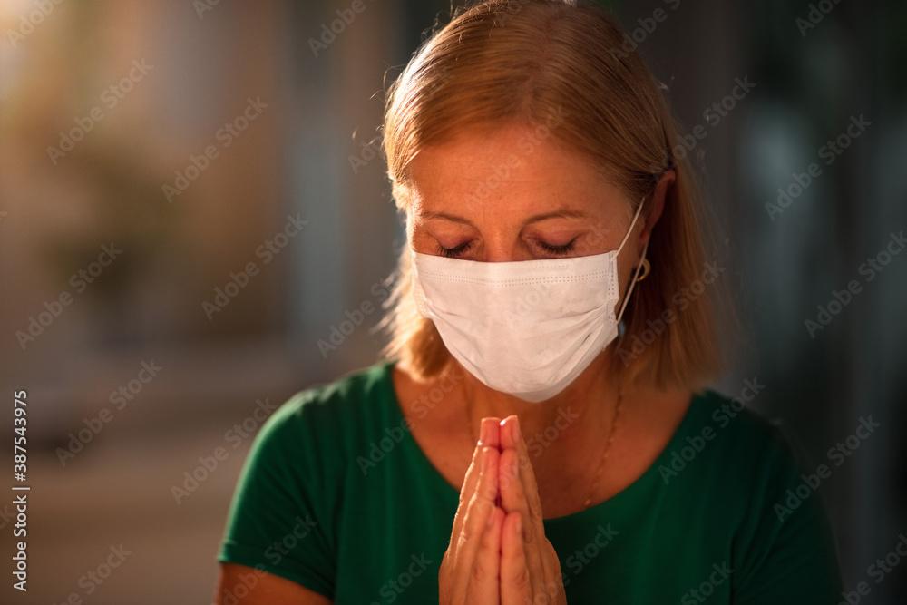 Fototapeta Woman in face mask praying for