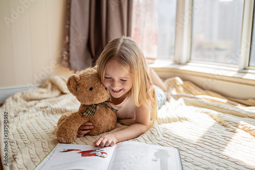 Fotografía Cute little caucasian girl in casual clothes reading a book with stuffed teddy bear toy and smiling while lying on a floor near window in the room