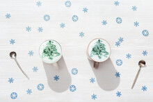Top View Of Cup Of Coffee Cappuccino With Pattern New Year Tree On White Wooden Table Decorated Blue Snowflakes.