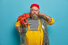 Strict Serious Bearded Sailor Curls Mustache Frowns Eyebrows And Looks Directly At Camera Poses With Red Octopus On Shoulder Uses Fishing Net During Marine Journey. Sea Voyage Adventure Trip