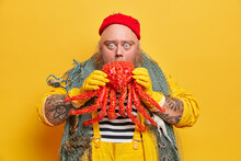 Shocked Bearded Sailor Stares Bugged Eyes Directly At Camera Holds Red Octopus Carries Fishing Net Around Neck Caught Big Marine Creature Isolated Over Yellow Background. Emotional Mariner In Overalls