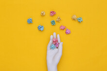 White Mannequin Hand Holding Crumpled Colored Paper Balls On Yellow Background