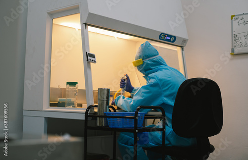 A scientist in PPE safty uniform pipetting sample experiment in biological safety cabinet (BSC) Fototapet